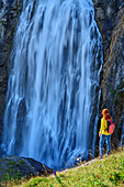 Woman hiking stands in meadow and looks at waterfall, Engstligenfall, Adelboden, Bernese Alps, Bern, Switzerland