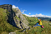 Man and woman while hiking sit on heel and look at mountains, Engstligenalp, Adelboden, Bernese Alps, Bern, Switzerland
