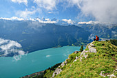 Woman while hiking sits on meadow ledge and looks out over Lake Brienz and the Bernese Alps in the background, from Augstmatthorn, Emmental Alps, Bern, Switzerland