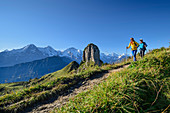 Man and woman hiking with Gumihorn in the middle distance, Eiger, Mönch and Jungfrau in the background, from Schynigen Platte, Grindelwald, Bernese Oberland, UNESCO World Natural Heritage Swiss Alps Jungfrau-Aletsch, Bernese Alps, Bern, Switzerland