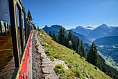 Red wagon of the rack railway travels to Schynige Platte, Bernese Alps in the background, from Schynigen Platte, Grindelwald, Bernese Oberland, UNESCO World Natural Heritage Swiss Alps Jungfrau-Aletsch, Bernese Alps, Bern, Switzerland