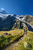 Man and woman hiking up to the Glecksteinhütte, Klein Schreckhorn in the background, Glecksteinhütte, Bernese Oberland, UNESCO World Natural Heritage Swiss Alps Jungfrau-Aletsch, Bernese Alps, Bern, Switzerland
