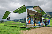 Several people visit Spiegelhaus, Mirror House, architect: Doug Aitken, Gstaad, Simmental, Bernese Alps, Bern, Switzerland