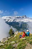 Mann und Frau beim Wandern sitzen auf Bergwiese und blicken auf Wolkenmeer mit Dents du Midi, vom Dent de Morcles, Berner Alpen, Vaud, Waadtland, Schweiz