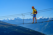 Woman on the Gemmi adventure via ferrata goes over rope bridge, Walliser Alps with cathedral and Weisshorn in the background, Gemmi, Bernese Alps, Wallis, Switzerland