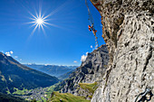 Woman climbs on overhanging ladder on adventure via ferrata Gemmi, Leukerbad and Valais Alps in the background, Gemmi, Bernese Alps, Valais, Switzerland