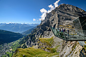 Several people stand on the Gemmi viewing platform and look out over Leukerbad and the Valais Alps, Gemmi, Bernese Alps, Valais, Switzerland
