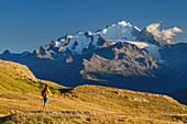 Woman hiking with cathedral in the background, Wiwannihütte, Bernese Alps, Valais, Switzerland