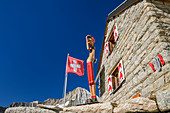 Hut Baltschiederklause with Swiss flag and wooden figure, Baltschiederklause, Bernese Alps, Valais, Switzerland