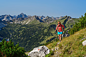 Woman hiking up to Litnisschrofen, Hochvogel in the background, Litnisschrofen, Tannheimer Berge, Tyrol, Austria