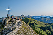 Several people sit on the summit of Litnisschrofen, Gimpel, Köllenspitze and Gehrenspitze in the background, Litnisschrofen, Tannheimer Berge, Tyrol, Austria