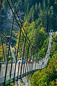 Several people walk over the Highline 179 rope bridge, Ehrenberg, Reutte, Tyrol, Austria