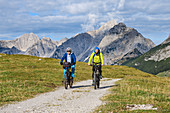 Two mountain bikers ride on Almstrasse, Karwendel in the background, Hochalmsattel, Karwendel, Karwendel Nature Park, Tyrol, Austria