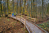 Man and woman hiking on forest promenade through forest, Hainich National Park, Thuringia, Germany