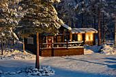 Kleines Ferienhaus in der Wintersonne im Wald, Slagnäs, Lappland, Schweden