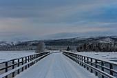 Verschneite Brücke über einen See im Winter in Lappland, Arjeplog, Schweden
