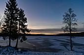 Morgendämmerung über einem vereisten See bei Lycksele, Västerbottens Län, Schweden