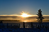 Sun and clouds over a frozen lake near Dorotea, Lapland, Sweden