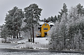 Sweden house by the lake in a snowy winter landscape, near Vilhelmina, Lapland, Sweden