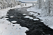 A river in winter surrounded by ice and snow in Lapland, Arjeplog, Sweden