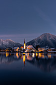 View over the wintry Tegernsee to the village of Rottach-Egern with the church Sankt Laurentius, Bavaria, Germany.