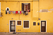 View of a yellow house facade with clothesline in Cannaregio, Venice, Veneto, Italy, Europe