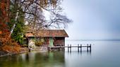 Boathouse in autumn with morning mist on Lake Starnberg, Garatshausen, Bavaria, Germany