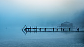 Boathouse with jetty in the fog on Lake Starnberg, Garatshausen, Bavaria, Germany