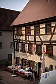 "Guests sit in the outdoor area of the historic ""Scharfeck"" restaurant in Fridingen an der Donau, Baden-Württemberg, Germany"