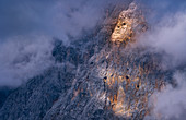 Evening sun illuminates the cloud-covered flank of the Zugspitze, Ehrwald, Tyrol, Austria, Europe