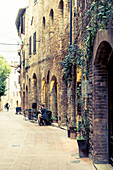 Sidewalk cafe in the alleys of San Gimignano, Province of Siena, Tuscany, Italy