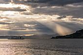Ferry in dramatic lighting, Garda, Lake Garda, Province of Verona, Italy