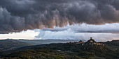 Dramatic cloud mood over a castle in Val d'Orcia, Tuscany, Italy