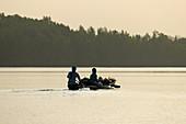 Gambia; Western Region; on the Bintang Bolong; two men sit in a fully loaded boat; drive towards Bintang
