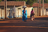 Gambia; Central River Region; Main street of Kuntaur; Married couple with luggage on their heads; Street scene in the morning sun;