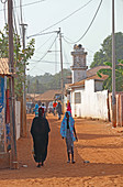 Gambia; Capital Region Banjul; Street scene in Bakau, near the Kachikally crocodile pool; in the foreground a woman in a black dress and a girl in a turquoise headscarf;