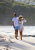 A couple walking the beach, sun against their back. St. Barths.