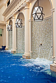 Spouts of water cascading into an interior pool decorated with mosaics and columns. Bath, United Kingdom