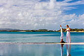 A yoga teacher gives instructions to a guests on a deck, set between a pool and the ocean. Antigua, West Indies.