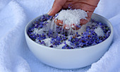 A woman´s hand in a bowl with sea-salt and blue flowers. Algarve, Portugal.