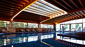 Indoor pool, with rooftop lighting and large windows illuminating the wooden structure, Madrid, Spain.