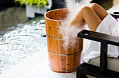 A woman having a footbath, in wooden barrel , with steam billowing. Horizontal. Kuala Lumpur, Malaysia.