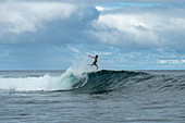 A surfer seems to be able to walk on the water - on a breaking wave in the surfing area Teahupoo, Tahiti Iti, Tahiti, Windward Islands, French Polynesia, South Pacific