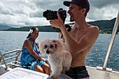 Photographer and small dog during boat excursion, Tahiti Iti, Tahiti, Windward Islands, French Polynesia, South Pacific