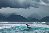 Surfer on wave in Teahupoo surfing area with storm clouds and mountains behind, Tahiti Iti, Tahiti, Windward Islands, French Polynesia, South Pacific
