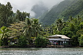 House on the edge of the lagoon with a mountain backdrop, Tahiti Iti, Tahiti, Windward Islands, French Polynesia, South Pacific