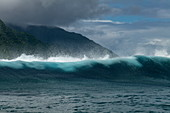 Breaking wave in the Teahupoo surfing area in front of a mountain backdrop, Tahiti Iti, Tahiti, Windward Islands, French Polynesia, South Pacific