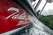 Low view of the side of a red tour boat with water spray, Tahiti Iti, Tahiti, Windward Islands, French Polynesia, South Pacific