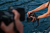 Panasonic Lumix S1R camera in hands of photographer on tour boat, Tahiti Iti, Tahiti, Windward Islands, French Polynesia, South Pacific