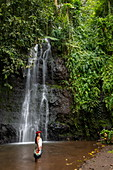 Beautiful young Tahitian woman in front of waterfall in 'The Water Gardens of Vaipahi', Teva I Uta, Tahiti, Windward Islands, French Polynesia, South Pacific